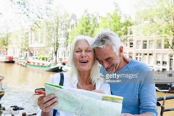 Netherlands, Amsterdam, happy senior couple with map at town canal