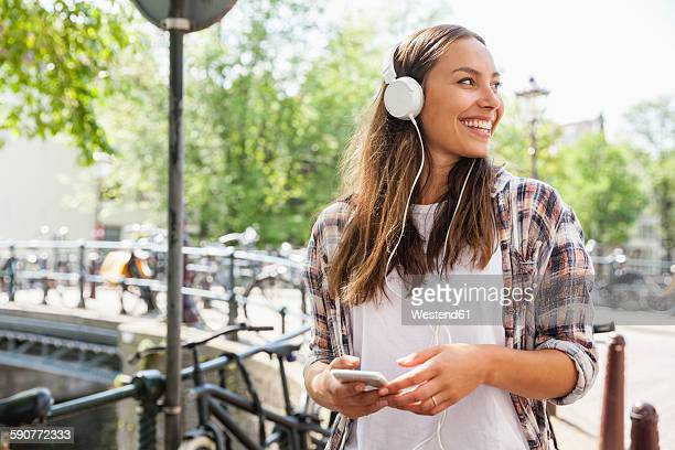 Netherlands, Amsterdam, happy young woman with headphones