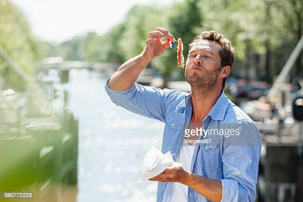 netherlands, amsterdam, man eating matjes herring - dutch culture stock photos and pictures