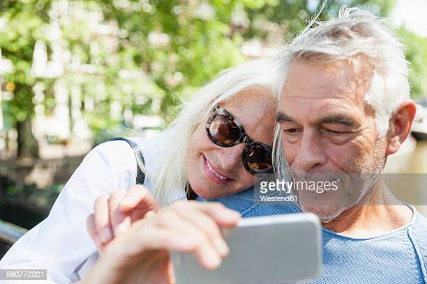 Netherlands, Amsterdam, senior couple taking a selfie at town canal