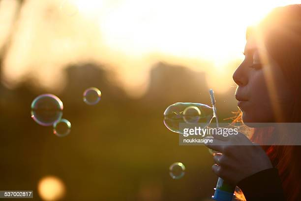 Netherlands, Amsterdam, Side view of young woman blowing bubbles