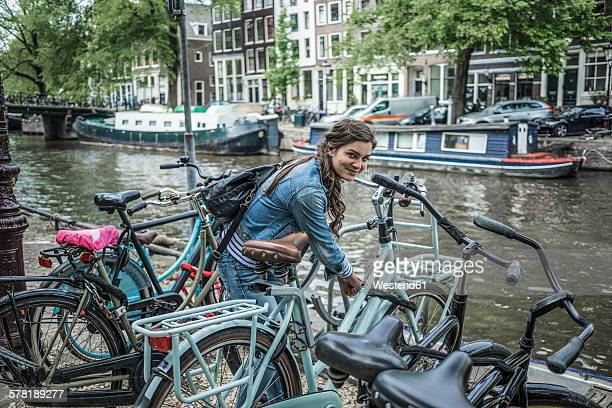 Netherlands, Amsterdam, smiling woman locking her bicycle in front of town canal