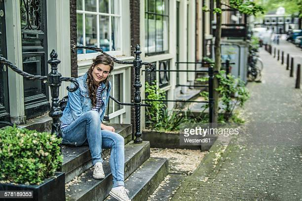 Netherlands, Amsterdam, smiling woman sitting on steps in front of house