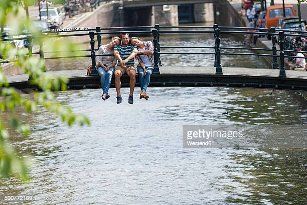 Netherlands, Amsterdam, three happy friends sitting on bridge at town canal