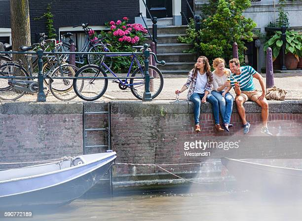 netherlands, amsterdam, three happy friends sitting with drinks at town canal - amsterdam stock pictures, royalty-free photos & images