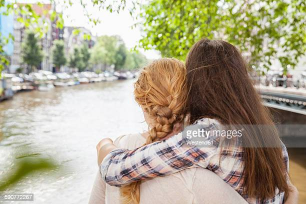 Netherlands, Amsterdam, two women embracing at town canal