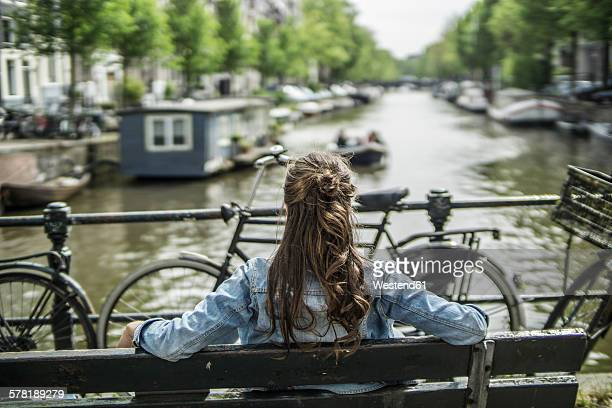 Netherlands, Amsterdam, woman ralxing on a bench in front of town canal