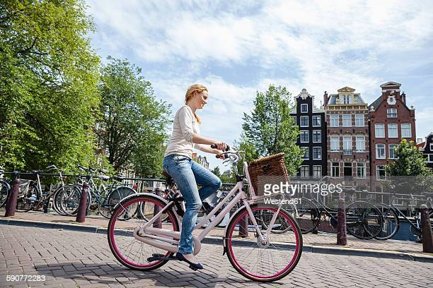Netherlands, Amsterdam, woman riding bicycle in the city