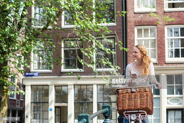 Netherlands, Amsterdam, woman with bicycle and cell phone in the city