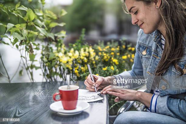 netherlands, amsterdam, woman writing postcards in a street cafe - answering stock pictures, royalty-free photos & images