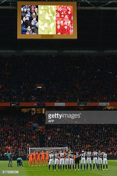 Netherlands' and France's players observe a minute of silence in memory of the victims of the March 22 Brussels attacks prior to the friendly...