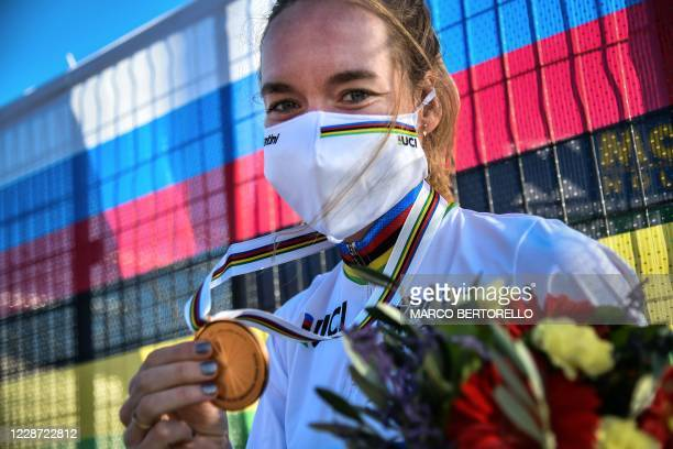 Netherlands' Anna van der Breggen, wearing a face mask, poses with her medal after winning the Women's Elite Road Race, a 143-kilometer route around...