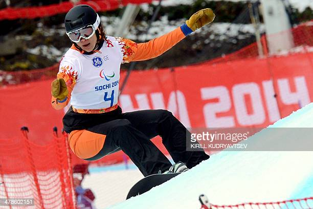 Netherlands' Bibian MentelSpee competes to win during the Women's Para Snowboard Cross Standing event during the Sochi Paralympics at the Rosa Khutor...