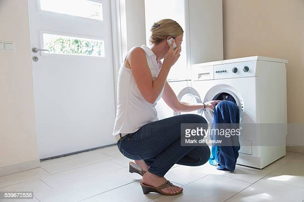 Netherlands, Brabant, Goirle, Woman taking laundry out of washing machine