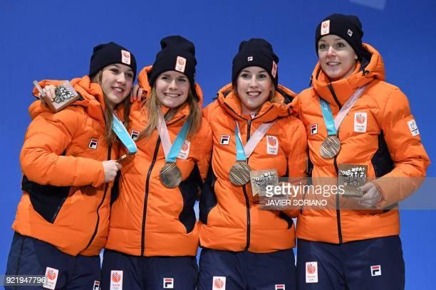 Netherlands' bronze medallists Suzanne Schulting, Yara van Kerkhof, Lara van Ruijven and Jorien ter Mors pose on the podium during the medal ceremony...