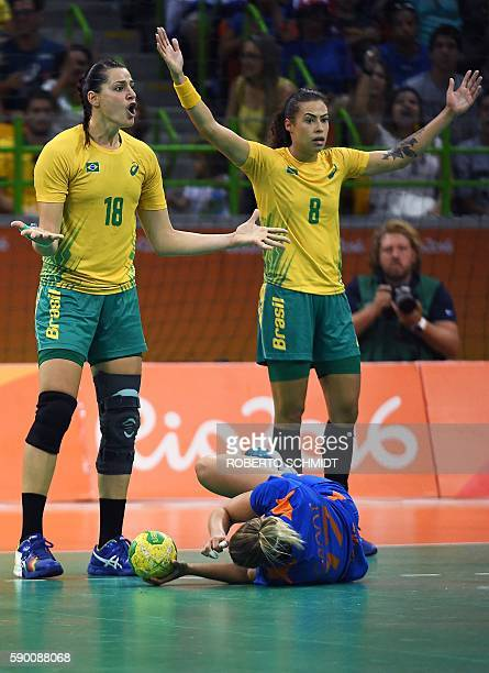 Netherlands' centre back Nycke Groot lies on the ground after being fouled past Brazil's right wing Eduarda Amorim and Brazil's left wing Fernanda...