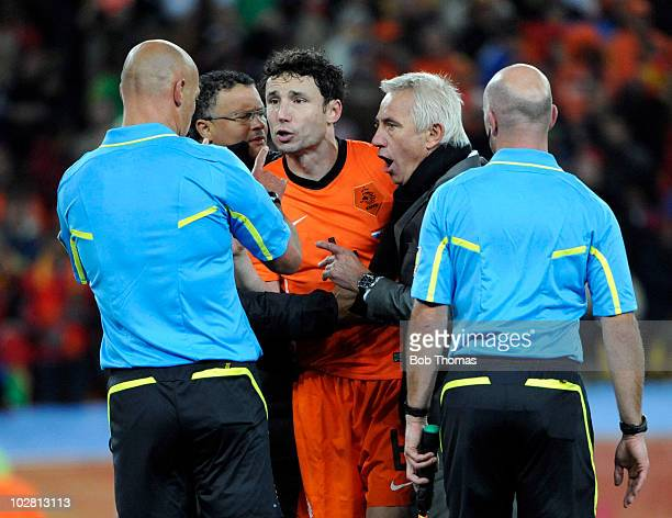 Netherlands coach Bert Van Marwijk together with player Mark Van Bommel make a point to referee Howard Webb after the 2010 FIFA World Cup Final...