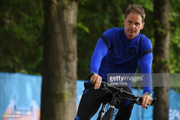 Netherlands' coach Frank de Boer rides a bike as he leaves their MD-1 training session in Zeist on June 12, 2021 on the eve of their UEFA EURO 2020...