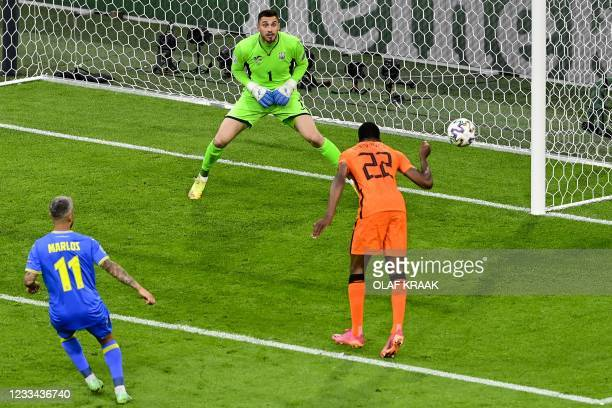 Netherlands' defender Denzel Dumfries heads the ball during the UEFA EURO 2020 Group C football match between the Netherlands and Ukraine at the...