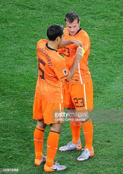 Netherlands' defender Giovanni van Bronckhorst hands the captain's armband to Netherlands' midfielder Rafael van der Vaart during extra-time in the...