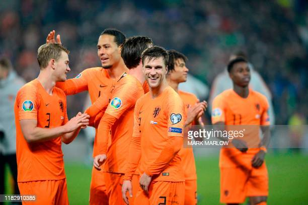 Netherlands' defender Joel Veltman and teammates celebrate their qualification for the finals on the pitch after the Euro 2020 qualification football...