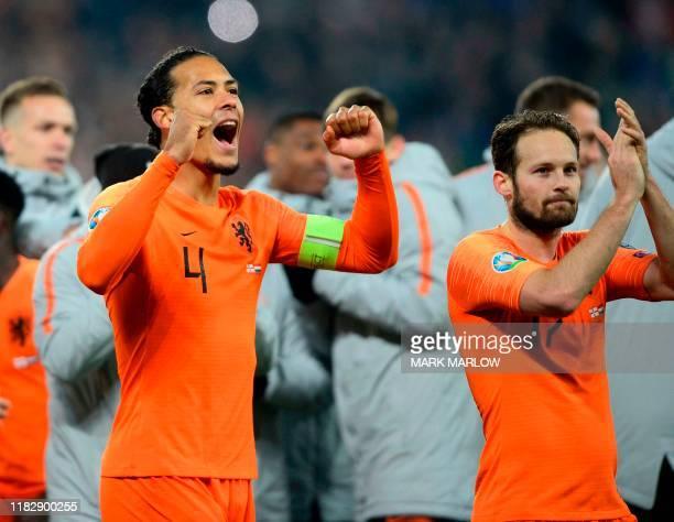 Netherlands' defender Virgil van Dijk and Netherlands' defender Daley Blind celebrate their qualification for the finals on the pitch after the Euro...