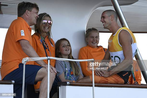 Netherlands' Dorian Van Rijsselberghe is congratulated by Netherland's King WillemAlexander and Queen Maxima after he won the RSX Men sailing final...