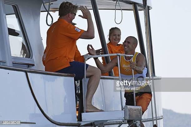Netherlands' Dorian Van Rijsselberghe is greetes by Netherland's King WillemAlexander after he won the RSX Men sailing final race on Guanabara Bay in...