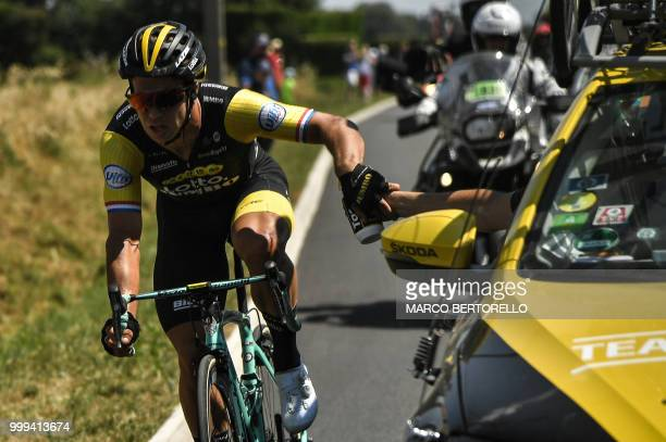 Netherlands' Dylan Groenewegen his left knee injured after crashing picks a water bottle as he catches up with the pack during the ninth stage of the...