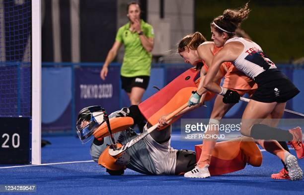 Netherlands' Felice Albers vies for the ball with Britain's goalkeeper Madeleine Claire Hinch and player Anna-Frances Toman during their women's pool...