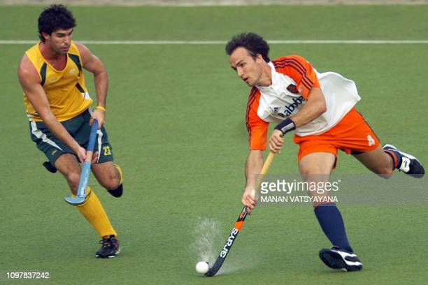 Netherland's field hockey player Karel Klaver controls the ball past Australian Mathew Wells during their Champions Trophy match in Chennai 14...