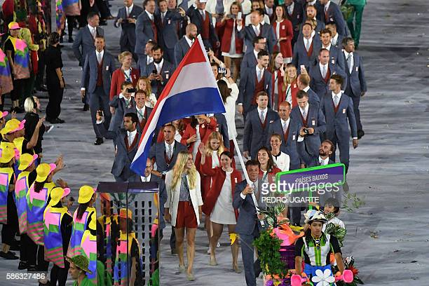 Netherlands' flagbearer Jeroen Dubbeldam leads his delegation during the opening ceremony of the Rio 2016 Olympic Games at the Maracana stadium in...