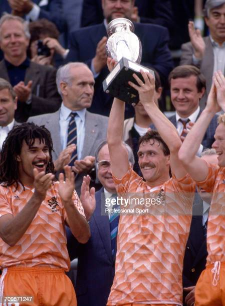 Netherlands football team captain Ruud Gullit applauds as Jan Wouters raises the UEFA European Championship trophy in the air after Netherlands beat...