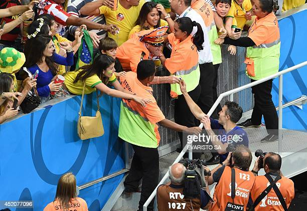 Netherlands' forward and captain Robin van Persie hands a fan his captian's arm band after winning the third place playoff football match between...