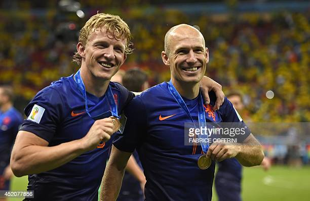 Netherlands' forward Arjen Robben and Netherlands' defender Dirk Kuyt salute the crowd after winning the third place playoff football match between...