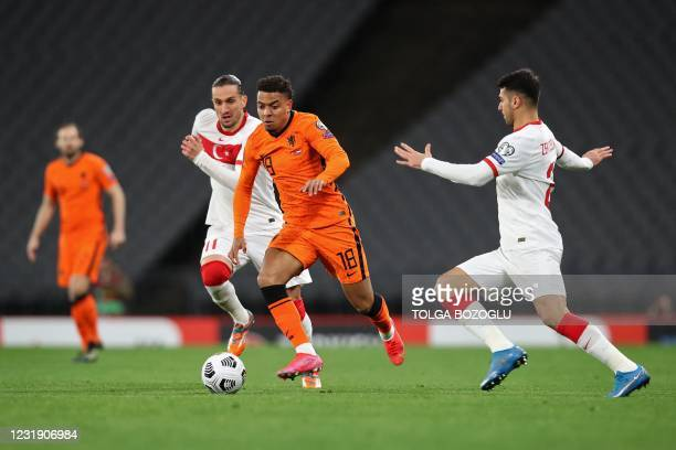 Netherlands' forward Donyell Malen is challenged by Turkey's forward Yusuf Yazici and Turkey's defender Zeki Celik during the FIFA World Cup Qatar...