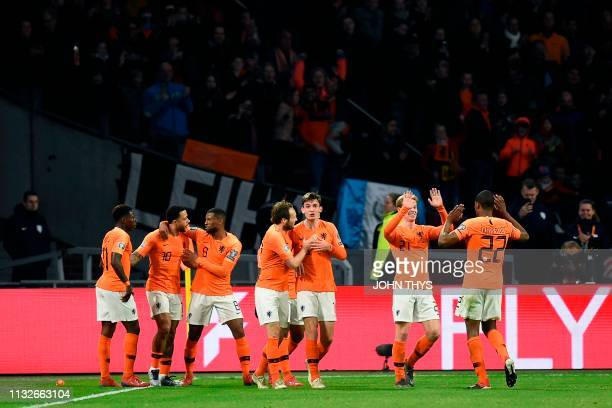Netherlands' forward Memphis Depay celebrates with teammates after scoring the equalizer during the UEFA Euro 2020 Group C qualification football...