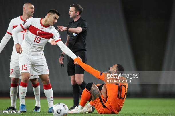 Netherlands' forward Memphis Depay is helped by Turkey's defender Ozan Kabak after being fouled during the FIFA World Cup Qatar 2022 qualification...