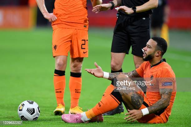 Netherlands' forward Memphis Depay reacts as he sits on the ground during the UEFA Nations League football match between The Netherlands and Bosnia...