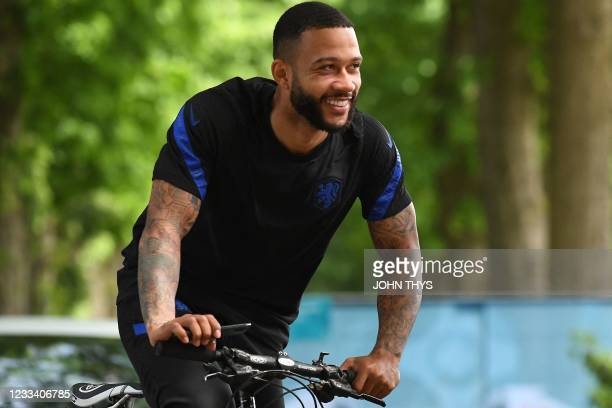 Netherlands' forward Memphis Depay rides a bike as he leaves their MD-1 training session in Zeist on June 12, 2021 on the eve of their UEFA EURO 2020...