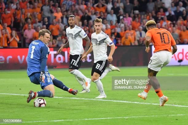 Netherlands' forward Memphis Depay scores a goal despite Germany's goalkeeper Manuel Neuer during the UEFA Nations League football match between...