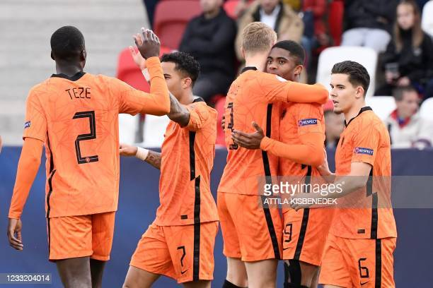 Netherlands' forward Myron Boadu celebrates with teammates after scoring the 1-1 goal during the UEFA Under21 Championship quarter-final football...