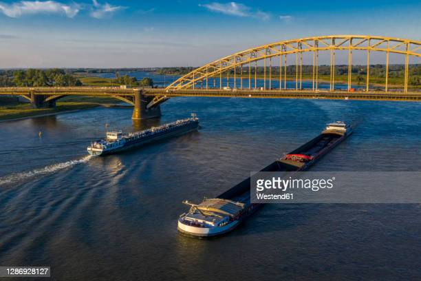 netherlands, gelderland, nijmegen, aerial view of barge and container ship sailing under bridge on river waal - nijmegen stock pictures, royalty-free photos & images