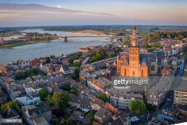 netherlands, gelderland, nijmegen, aerial view of saint stephens church and surrounding buildings at dusk - nijmegen stock pictures, royalty-free photos & images