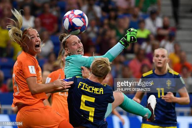 Netherlands' goalkeeper Sari van Veenendaal and Netherlands' defender Stefanie van der Gragt vie for the ball with Sweden's defender Nilla Fischer...