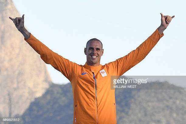 Netherlands' gold medallist Dorian Van Rijsselberghe poses on the podium after the RSX Men sailing final race on Guanabara Bay in Rio de Janerio...