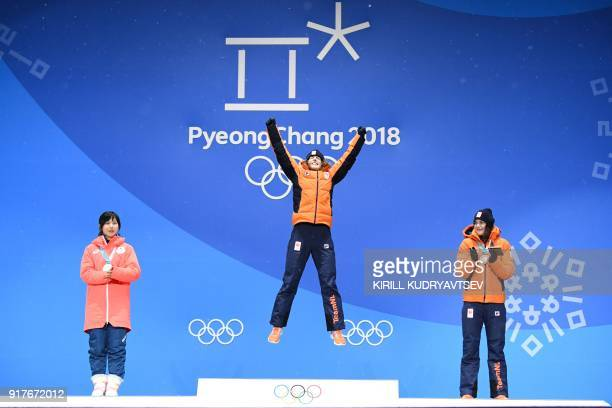 Netherlands' gold medallist Ireen Wust jumps on the podium between Japan's silver medallist Miho Takagi and Netherlands' bronze medallist Marrit...