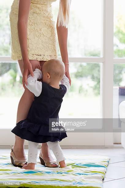 Netherlands, Helvoirt, Girl hiding in mother's legs