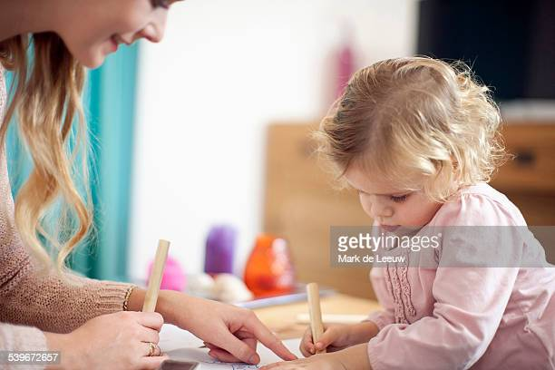 Netherlands, Helvoirt, Woman teaching young girl at home