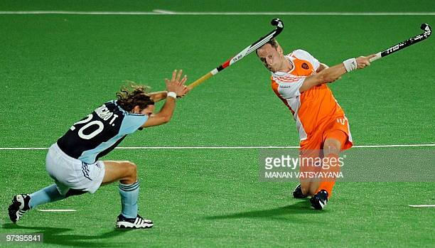 Netherlands hockey player Taeke Taekema lofts the ball as Argentinian hockey player Tomas Argento looks on during their World Cup 2010 match at the...